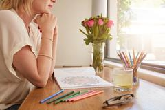 Woman sitting at a table and thinking with adult coloring book Stock Photos