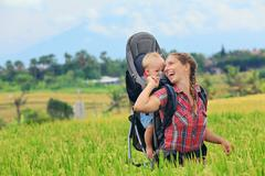 Happy woman hold child in backpack baby carrier Stock Photos