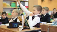 Young schoolboy wants to answer the question and lifts the hand. Russian school Stock Footage