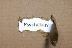 The word psychology appearing behind torn paper. - stock photo