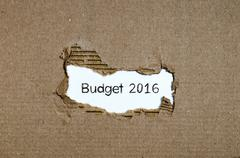 The word budget 2016 appearing behind torn paper Stock Photos
