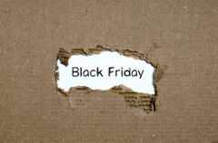 The word black friday appearing behind torn paper Stock Photos
