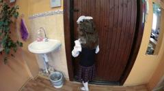Little girl in uniform looks through the class door in school hall. Russia - stock footage