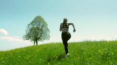 Young woman jogs up a hill Stock Footage