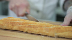 Chef slicing crusty baguette bread Stock Footage