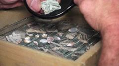 ARCHEAEOLOGIST STUDYING POTTERY SHARDS, primitive art - stock footage