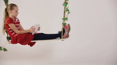 Child sitting on swing with digital tablet Stock Footage