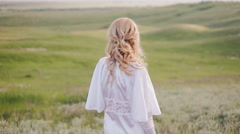 Girl in a field turn round and looking at the camera Stock Footage