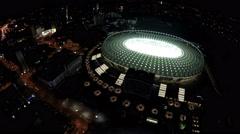 Oval-shaped illuminated football stadium, aerial view on beautiful night city - stock footage