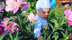 A child playing in the garden flowers Stock Footage