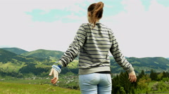 4K. Young girl tourist raises hands up, enjoys life in mountain hills. Steady s Stock Footage