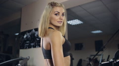 Sexy girl in gym posing - stock footage
