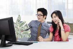 Businesspeople earn money online on computer Stock Photos