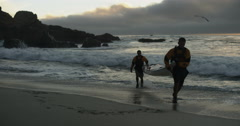 Two Men Silhouette Carrying Sea Kayak From Stormy Ocean In Slow Motion Arkistovideo