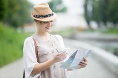 Young traveler woman holding map and phone during abroad trip - stock photo