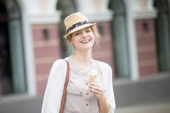 Headshot portrait of young happy woman eating ice-cream cone in summer - stock photo