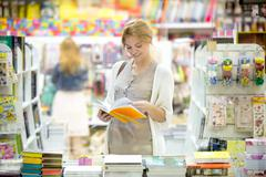 Portrait of young happy woman shopping in bookstore Stock Photos