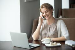 Half-length portrait of happy woman using phone and laptop in cafe - stock photo