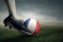 Soccer player kicking ball toward a goal post Stock Photos