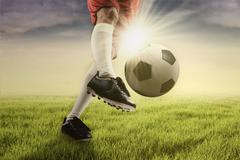 Soccer player kicking the ball at the green field - stock photo