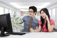 Two workers making money online - stock photo