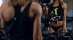 Sexy girl doing curls on biceps with dumbbells - stock footage