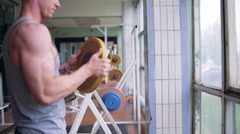 Athletic man is putting plates on barbell - stock footage
