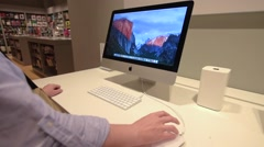 Woman looking at the specifications and testing the new iMac Stock Footage