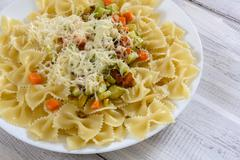 Pasta farfalle with slices of vegetables on a wooden background. Stock Photos