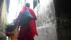 Pan shot of Indian sadhus walking through the alley.. Stock Footage
