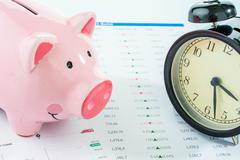 Alarmclock with piggybank, stock market Stock Photos