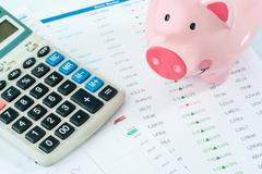 Piggybank and calculator, stock market Stock Photos
