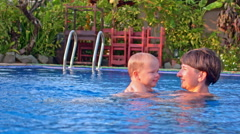 mother tossing up toddler boy in water - stock footage