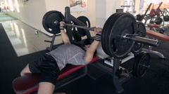 Young Male Athlete Raises The Barbell Lying In The Gym Stock Footage
