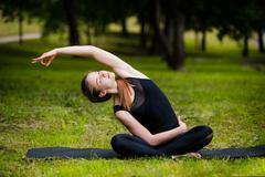 Beautiful young woman doing stretching exercise on green grass at park. Yoga Kuvituskuvat