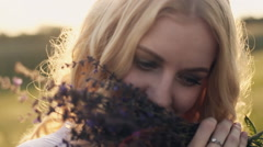blonde girl with blue eyes smelling a herbs bouquet - stock footage