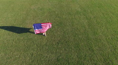 Aerial Circle Flying Around Female Athlete Holding American Flag - stock footage