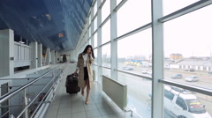 Woman in beige coat talks on phone and goes through airport Stock Footage