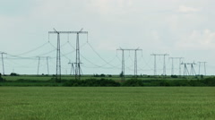 Power transmission line. Electric lines in the green field. - stock footage