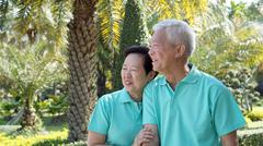 Asian senior couple smiling togher in green nature background Stock Photos