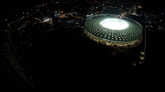 Huge sports arena shining with lights in heart of night megalopolis, aerial shot Arkistovideo