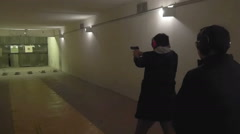 The instructor watches as the man shoots from a gun in shooting gallery Stock Footage