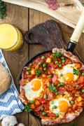 Baked eggs with chorizo, potatoes and tomatoes in a pan on the table. top view Stock Photos