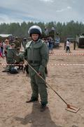 Man - visitor of show tries on the sapper suit - stock photo