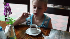 Boy at the Table Drinking Tea Stock Footage