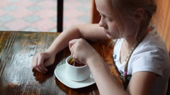Girl at the Table Drinking Tea Stock Footage