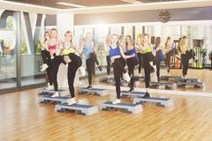 Group of women, step aerobics in fitness club - stock photo