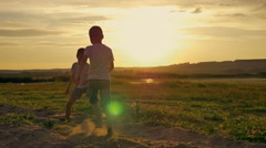 Two happy child running around and jumping in the park. On the field, the two Stock Footage