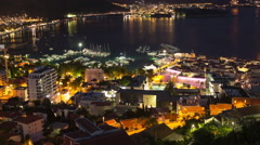 Medieval walled old city of the Budva with night illumination is near sea port Stock Footage