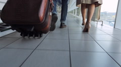 Couple of people walks through airport carrying luggage with them Stock Footage